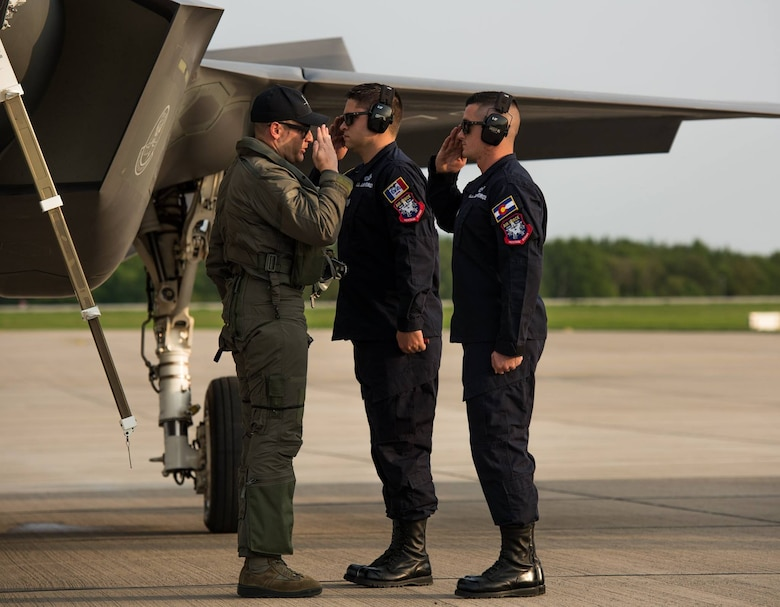 "Capt. Andrew ""Dojo"" Olson, F-35 Heritage Flight Team commander and pilot, salutes  both Staff Sgt. Patrick Murphy and Staff Sgt. John Baker, F-35 Heritage Flight Team crew chiefs, upon arrival for the 2018 Berlin Air and Trade Show at the Berlin Schönefeld Airport, in Berlin, Germany, April 22, 2018. The Berlin Air and Trade Show provides an invaluable forum to demonstrate the types of weapons and technology that promote the goals of enhancing the security of our allies and improving interoperability. (U.S. Air Force photo by Airman 1st Class Alexander Cook)"