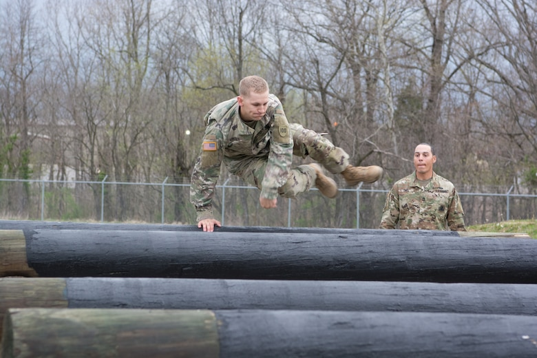 Staff Sgt. Ethan Kruger, with the Camp Parks Noncommissioned Officer Academy,  83rd U.S. Army Reserve Readiness Training Center, 100th Training Division, makes jumping logs look easy as he maneuvers through the obstacle course at the 80th Training Command's 2018 Best Warrior Competition at Fort Knox, Kentucky, April 14, 2018.  His sponsor (background) stays with Kruger throughout the entire competition. (U.S. Army Reserve photo by Maj. Addie Leonhardt, 80th Training Command)