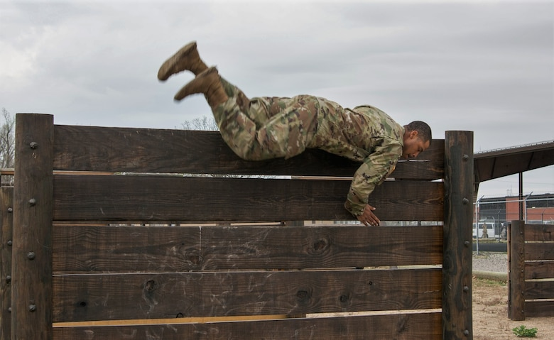 Staff Sgt. DeMarko Snow, assigned to Fort Dix Noncommissioned Officer Academy, 83rd U.S. Army Reserve Readiness Training Center, 100th Training Division, flips himself over a wall in the obstacle course portion of the 80th Training Command's 2018 Best Warrior Competition at Fort Knox, Kentucky, April 14, 2018. (U.S. Army Reserve photo by Maj. Addie Leonhardt, 80th Training Command)