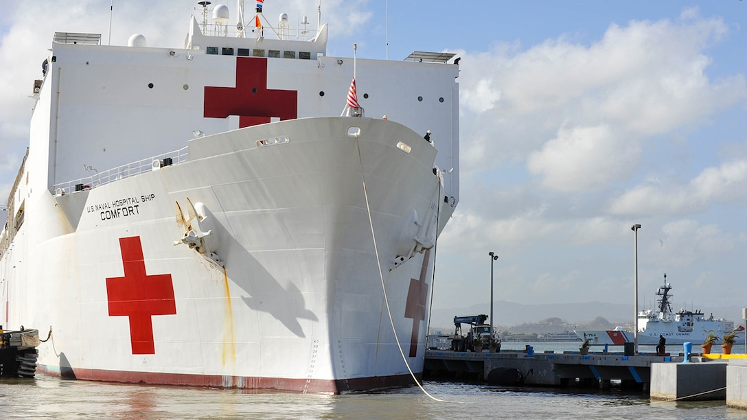 The hospital ship USNS Comfort, white with red crosses, is docked in Puerto Rico