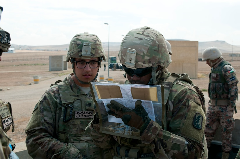 American Spc. Jason Durant of Headquarters and Headquarters Battery, 1st Battalion, 143rd Field Artillery Regiment, goes over the simulated battlefield where Jordanian and U.S. forces were practicing calling for indirect fire with Spc. Damek Jouan, HHB, 1-143 FAR, during an exercise at Jordan's Joint Training Center near Amman, Jordan, April 11, 2018. The bilateral training was part of the Jordan Operational Engagement Program and focused on the exchange of infantry tactics and techniques.