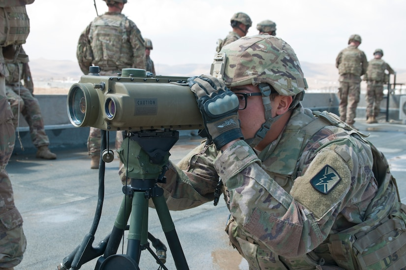 Specialist Damek Jouan, Headquarters and Headquarters Battery, 1st Battalion, 143rd Field Artillery Regiment, views a target through a lightweight laser designator rangefinder during an exercise at Jordan's Joint Training Center near Amman, Jordan, April 11, 2018. The bilateral training was part of the Jordan Operational Engagement Program and focused on the exchange of infantry tactics and techniques.