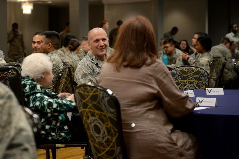 A man in the Airman Battle Uniform smiles at a woman with red hair wearing brown shawl and an elderly woman in a blue, white and black shirt.