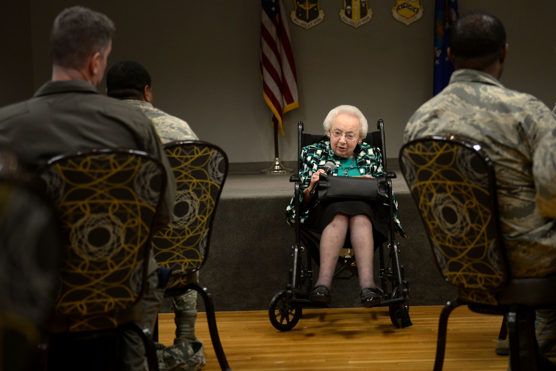 An elderly woman in a wheel chair wearing a blue, white and black shirt holds a microphone up to her mouth in front of numerous people in the Airman Battle Uniform.