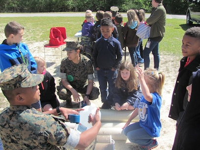 On Friday April 13, 2018 Marine Corps Engineer School supported Johnson Primary School Career Day by providing equipment for static displays and Marines capable of delivering information about the equipment and their job to the children. The intent of Johnson Primary Career Day was to provide their students insight and information about the occupations of some of the parents through static displays and interaction with service members with various Military Occupational Specialties (MOS). Sergeant Dionnhel D. Bareng and Staff Sergeant Zoyla V. Bocksnick, instructors with Utilities Instruction Company, talk to a group of students about their jobs as water support technicians.