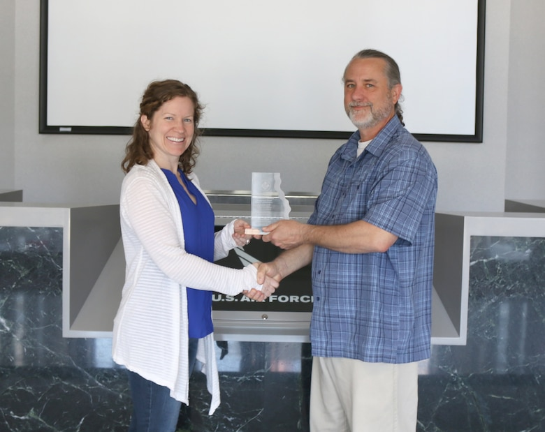 John Lamb, biologist at Arnold Air Force Base, displays his 2018 National Military Fish and Wildlife Association National Resources Conservation Management Award for Model Programs and Projects with Shannon Allen, Chief, National Environmental Policy Act, Natural and Cultural Resources, as she congratulates him. This award category recognizes resource managers who further natural resource management on military installations in support of the military mission through developing programs or projects which can serve as models for conservation on military installations. (U.S. Air Force photo/Deidre Ortiz)