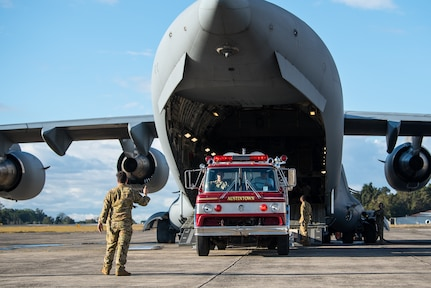 A firetruck is offloaded from an U.S. Air Force cargo plane.