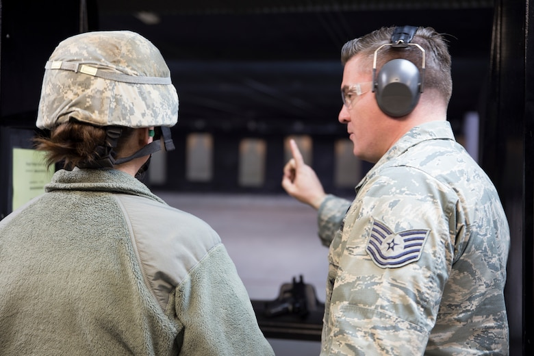 Tech Sgt. Sean Redden, of the 224th Air Defense Group in Rome, New York, assists Staff Sgt. Stephanie Lambert, 109th Airlift Wing Public Affairs photojournalist, with the pistol qualification portion of the German Armed Forces Forces Proficiency Badge on April 15, 2018, at the American Tactical Systems firing range in Green Island, New York.