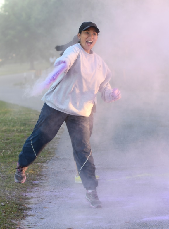 U.S. Air Force Chief Master Sgt. MaryAnn Navarro-Davis, 81st Mission Support Group superintendent, tosses purple powder on runners during the Air Force Assistance Fund Color Run at Keesler Air Force Base, Mississippi, April 20, 2018. The AFAF raises funds for charitable affiliates that provide support to Air Force families in need. (U.S. Air Force photo by Kemberly Groue)
