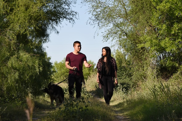Airman 1st Class Robby Agustin, 47th Operation Support Squadron aircrew flight equipment assistant, Irish Domingo, his spouse, and their dog Momo explore the nature trails at Laughlin Air Force Base, April 23, 2018. The couple enjoys the trails as an alternate to visiting the gym, as well as an opportunity for family time. (U.S. Air Force photo by Airman 1st Class Anne McCready)
