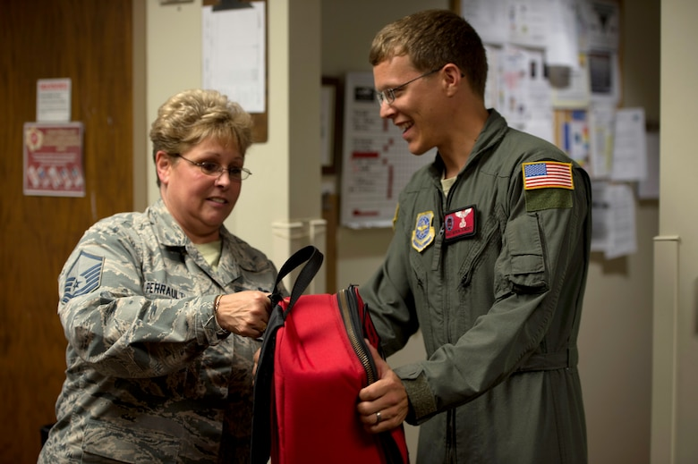 U.S. Air Force Master Sgt. Karen Perrault, NCO in charge of reserve component combat crew communications assigned to the 927th Operations Support Squadron, hands an aircrew kit to Master Sgt. Myron Somero, B-Flight chief assigned to the 50th Air Refueling Squadron, April 17, 2018 at MacDill Air Force Base, Fla.