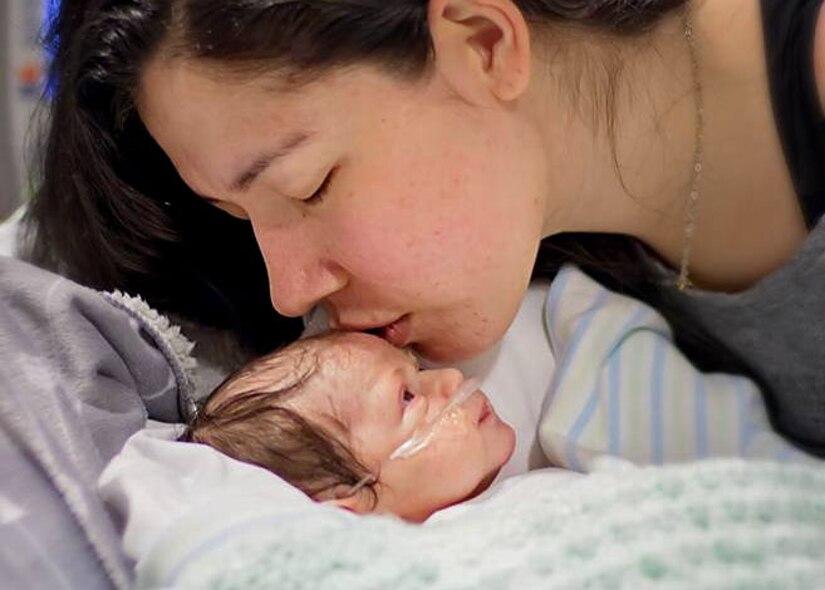 Ashley Mockovciak, Team Shaw spouse, kisses her son Noah Mockovciak in a hospital at Charleston, S.C., circa February 2017.