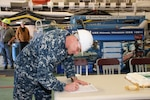 BATH, Maine -- Cmdr. John Bauer, DDG 1000 program manager's representative, signs paperwork accepting delivery of the future USS Michael Monsoor (DDG 1001).  Following a crew certification period, Michael Monsoor will transit to its homeport in San Diego, California, for commissioning in January 2019.