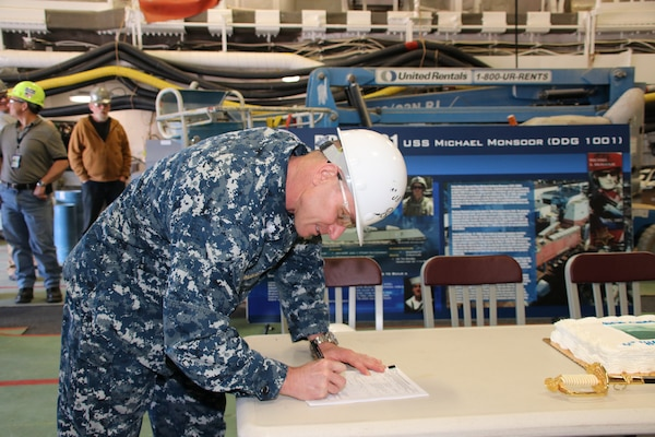 Cmdr. John Bauer, DDG 1000 program manager's representative, signs paperwork accepting delivery of the future USS Michael Monsoor (DDG 1001).  Following a crew certification period, Michael Monsoor will transit to its homeport in San Diego, California, for commissioning in January 2019.