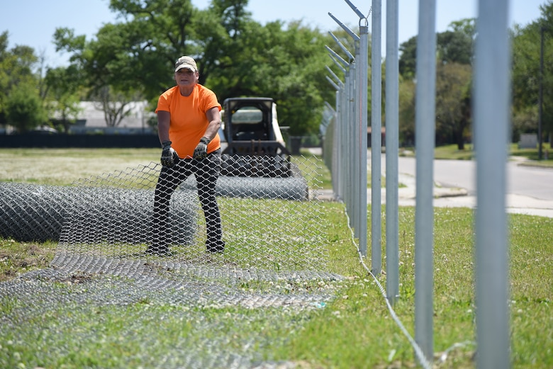 Jewell Gonzalez, Gulf Coast Fence Company laborer, unrolls fencing in the open grass area near the commissary at Keesler Air Force Base, Mississippi, April 10, 2018. The fence will serve as a perimeter around the site of the new Division Street Gate entrance construction. The estimated $37 million project will begin construction this summer. (U.S. Air Force photo by Kemberly Groue)