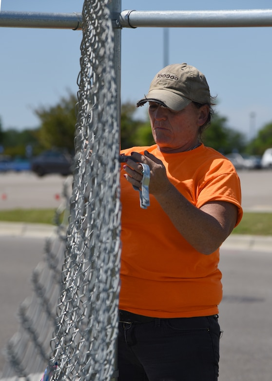 Jewell Gonzalez, Gulf Coast Fence Company laborer, secures fencing in the open grass area near the commissary at Keesler Air Force Base, Mississippi, April 10, 2018. The fence will serve as a perimeter around the site of the new Division Street Gate entrance construction. The estimated $37 million project will begin construction this summer. (U.S. Air Force photo by Kemberly Groue)