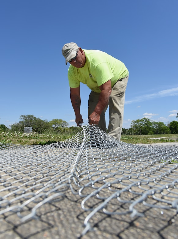 Donald Gonzalez, Gulf Coast Fence Company superintendent, assembles fencing in the open grass area near the commissary at Keesler Air Force Base, Mississippi, April 10, 2018. The fence will serve as a perimeter around the site of the new Division Street Gate entrance construction. The two-year project includes an expanded and enhanced boulevard along Division St. from I-110 to Forrest Ave. (U.S. Air Force photo by Kemberly Groue)