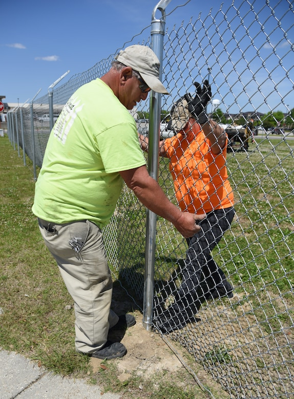 Donald Gonzalez, Gulf Coast Fence Company superintendent, and Jewell Gonzalez, Gulf Coast Fence Company laborer, installs fencing in the open grass area near the commissary at Keesler Air Force Base, Mississippi, April 10, 2018. The fence will serve as a perimeter around the site of the new Division Street Gate entrance construction. The two-year project includes an expanded and enhanced boulevard along Division St. from I-110 to Forrest Ave. (U.S. Air Force photo by Kemberly Groue)