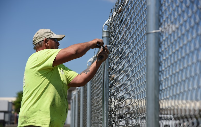 Donald Gonzalez, Gulf Coast Fence Company superintendent, secures fencing in the open grass area near the commissary at Keesler Air Force Base, Mississippi, April 10, 2018. The fence will serve as a perimeter around the site of the new Division Street Gate entrance construction. The two-year project includes an expanded and enhanced boulevard along Division St. from I-110 to Forrest Ave. (U.S. Air Force photo by Kemberly Groue)
