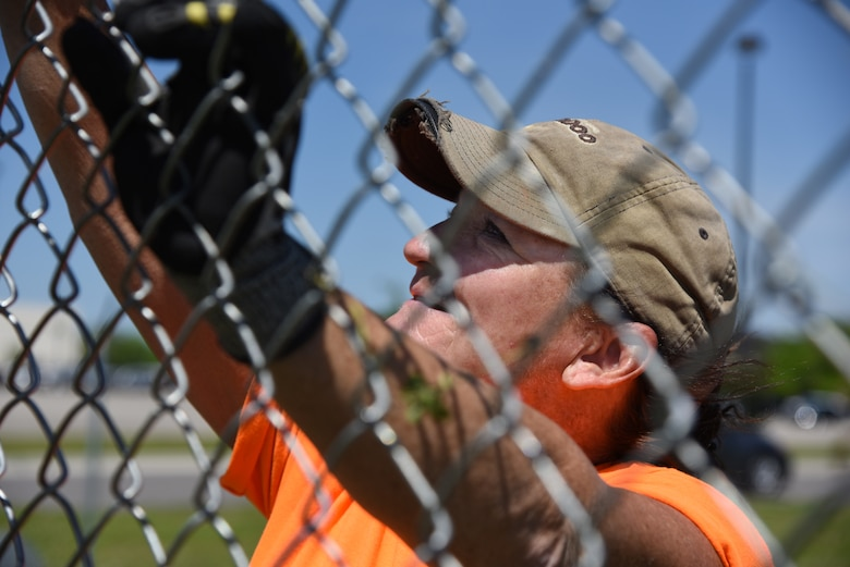 Jewell Gonzalez, Gulf Coast Fence Company laborer, installs fencing in the open grass area near the commissary at Keesler Air Force Base, Mississippi, April 10, 2018. The fence will serve as a perimeter around the site of the new Division Street Gate entrance construction. The estimated $37 million project will begin construction this summer. (U.S. Air Force photo by Kemberly Groue)