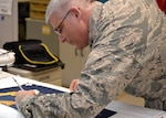 The 53rd Adjutant General of the Pennsylvania National Guard Air Force Maj. Gen. Anthony Carrelli signs a presidential flag being hand-embroidered at DLA Troop Support in Philadelphia April 16.