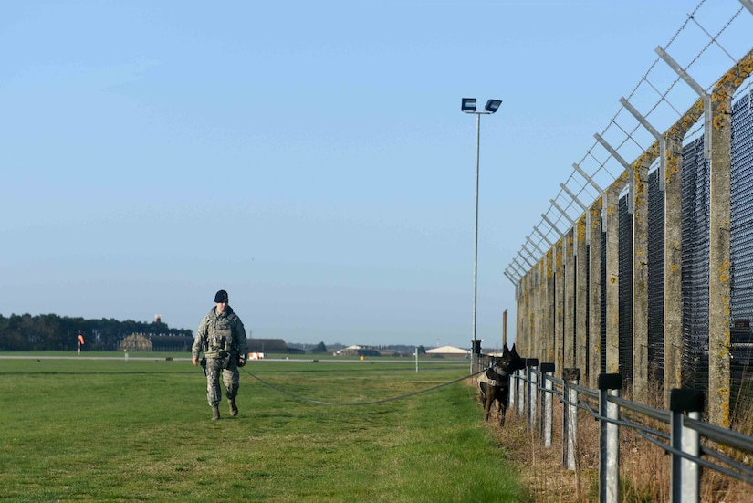 Air Force Staff Sgt. Bryce Bates, a 48th Security Forces Squadron military working dog handler, and his partner, Gorro, perform a perimeter check at Royal Air Force Lakenheath, England.