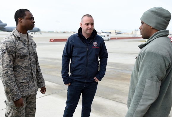 Aaron McAuley, center, a Belfast International Airport Rescue and Firefighting Service crew commander, stands with Senior Airmen Shannon Banks, left, and Danny Thomas, right, both 60th Civil Engineer Squadron firefighters during a meet and greet session April 11 at Travis Air Force Base, Calif. In addition to empowering each other through spirituality, Firefighters for Christ also encourages the exchanging of ideas and methods so as to keep the skills of each participating firehouse sharp and efficient. (U.S. Air Force photo by Airman 1st Class Christian Conrad)