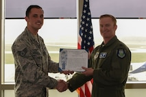 Lt. Col. Kit Conn, 436th Operations Support Squadron commander (right) presents Staff Sgt. Justin Stoudt, 436th OSS Radar Approach Control air traffic controller, with the Lt. Gen. Gordon A. Blake Aircraft Save Award April 19, 2018, at Dover Air Force Base, Del. Stoudt was presented the award for his impeccable composure and attentiveness during an emergency landing situation in October 2017. (U.S. Air Force photo by Airman 1st Class Zoe M. Wockenfuss)