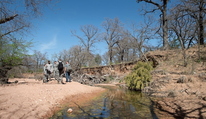 Senior Airman Philip Lee, a contracting specialist assigned to the 97th Contracting Squadron, leaps over a creek during a contracting contingency exercise, April 18, 2018, Fort Sill, Okla. Contracting Airmen from five different bases came together to exercise Operational Contract Support in a deployed environment. (U.S. Air Force photo by Airman Jeremy Wentworth)
