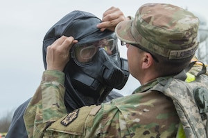 "Army Spc. Logan Lawrence adjusts the hazardous materials suit of Army Pvt. Brandon Cormeir, both from 3rd platoon, 22nd Engineer Clearance Company, before Cormeir enters the exercise ""hot zone"" during the Guardian Response 18 exercise at Muscatatuck Urban Training Center, Ind."