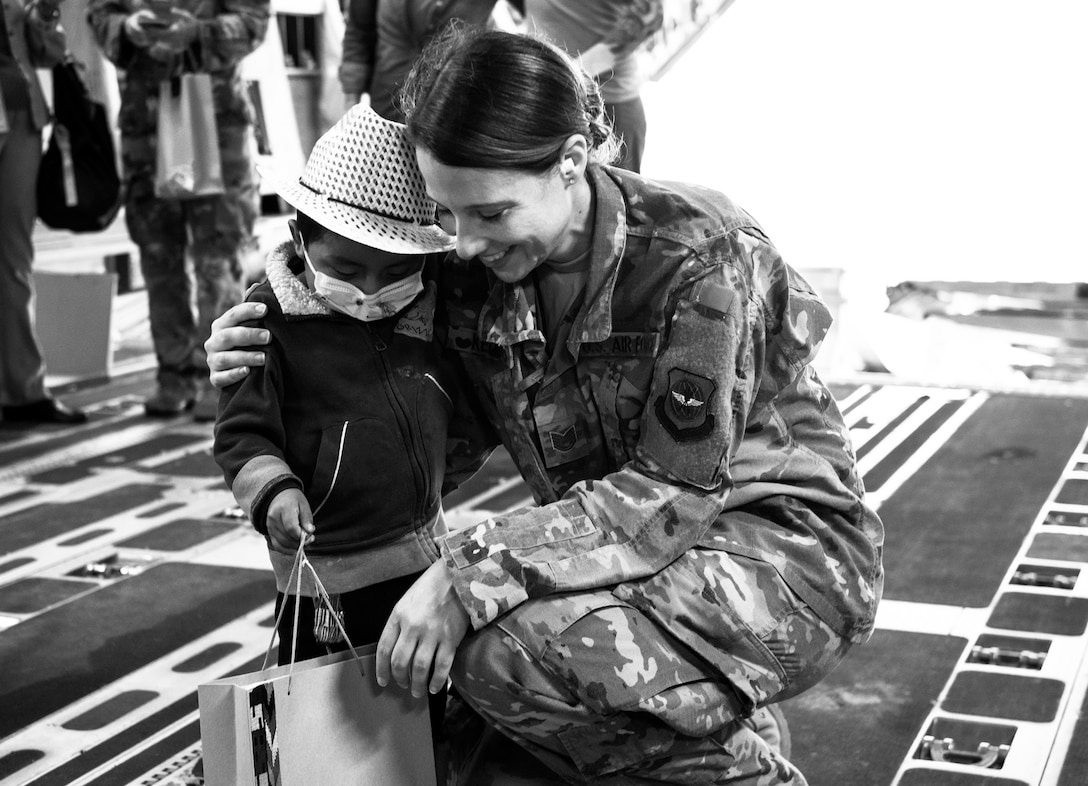 U.S. Air Force Tech. Sgt. Traci Keller, 60th Air Mobility Wing Public Affairs broadcast journalist, shares a moment with a local child after covering the delivery of emergency response vehicles through the Denton Program at La Aurora International Airport, Guatemala City, Guatemala, April 20, 2018. The Denton Program is a Department of Defense transportation program that moves humanitarian cargo, donated by U.S. based Non-Governmental Organizations to developing nations to ease human suffering. The emergency vehicles were donated by the Mission of Love Foundation, they are the largest user of the Denton Program, having delivered medical, relief and humanitarian supplies to needy communities throughout the world. (U.S. Air Force Photo by Master Sgt. Joey Swafford)
