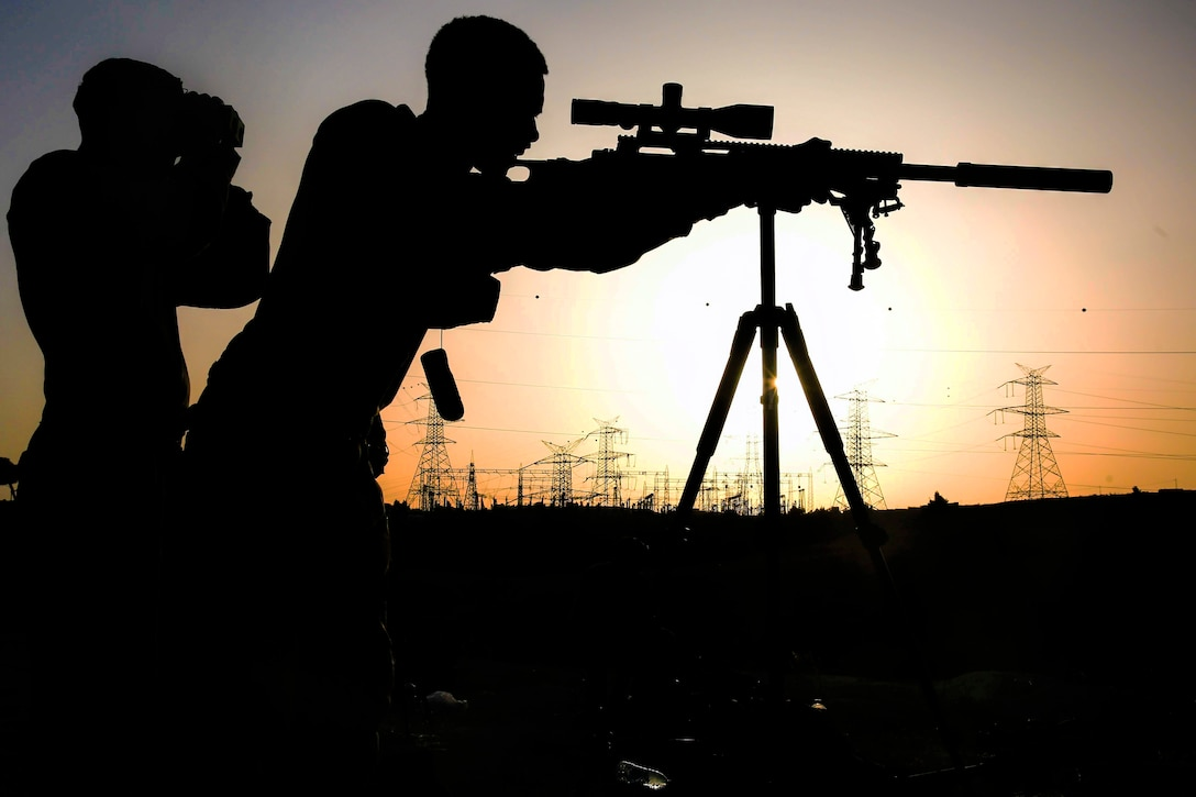 A Marine, shown in silhouette, looks through a sniper rifle scope, as someone looks through binoculars beside him.