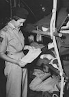 Australian and New Zealand Army Corps (ANZAC) Day is a time to honor members and reflect on the long-lasting partnership between ANZAC and the Air Force Medical Service, which reaches back to the Korean war when ANZAC and AFMS members worked together as allies. Pictured above, Australian flight nurse Nathalie Oldham, on temporary duty with the U.S. Air Force Medical Service, checks on her American patients before departing Korea for American hospitals in Japan. Oldham, with the Royal Australian Air Force Nursing Service, served with the AFMS for several months during the summer of 1952. During that time she observed many differences between the services, such as, unlike American flight nurses, the Australians did not receive flight pay and were not allowed to eat in the officer's mess. Oldham was also impressed with the Americans' larger medical aircraft and abundance of supplies. (U.S. Air Force photo)
