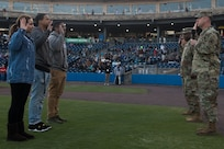 (Right) U.S. Army Col. Ralph Clayton, 733rd Mission Support Group commander, administers the oath of enlistment for three recruits at Fort Eustis Night during a Norfolk Tides game at Harbor Park, Virginia, April 21, 2018. Fort Eustis, Virginia is celebrating its 100 years and remembering the variety of missions it has supported since 1918. (U.S. Air Force photo by Senior Airman Derek Seifert)