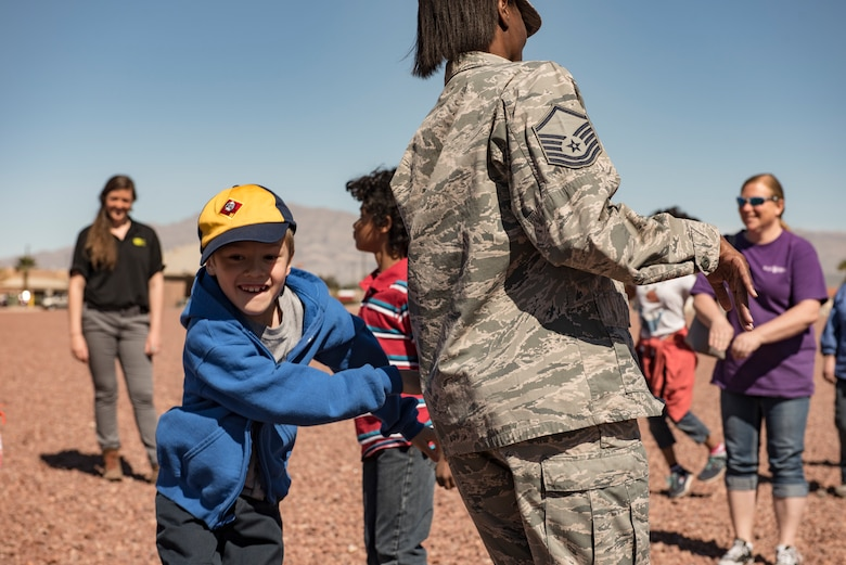 A child tags an Airman during a Leave No Trace workshop at Nellis Air Force Base, Nevada, March 28, 2018. The game simulated how invasive species can have a negative impact on the environment. (U.S. Air Force photo by Airman 1st Class Andrew D. Sarver)