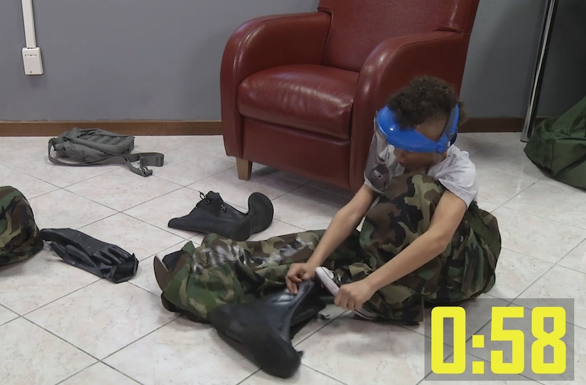A child sits on the floor and puts on military gear.