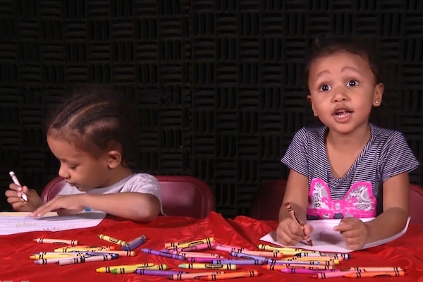 Two children draw at a table.