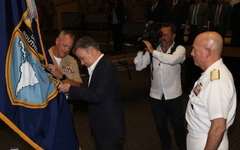 Colombian President Juan Manuel Santos pins the Orden of San Carlos  Medal to the U.S. Southern Command flag
