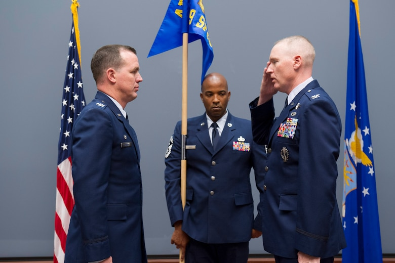 Col. Richard Mendez (right), commander of the newly-activated 709th Support Group, salutes and accepts command from Col. Steven M. Gorski (left), commander of the Air Force Technical Applications, Patrick AFB, Fla.  Holding the guidon is Senior Master Sgt. Braderick Adams, group first sergeant under Mendez' command.  (U.S. Air Force photo by Phillip C. Sunkel IV)