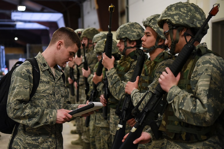 Cadet Maj. Avery Buggert, a member of the ROTC program at the University of North Dakota, inspects Airmen on Grand Forks Air Force Base, N.D., April 21, 2018. Buggert verified all Airmen had the correct weaponry and equipment to ensure they were prepared for a readiness exercise. (U.S. Air Force photo by Airman 1st Class Melody Wolff)