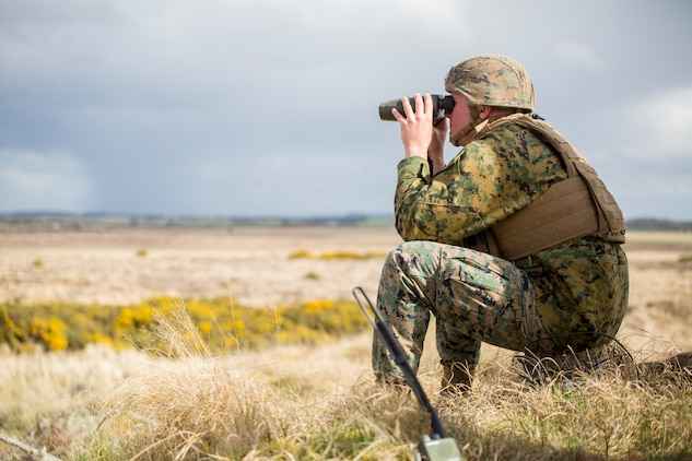 Lance Cpl. Dalton Vandervoort, a forward observer with 4th Air Naval Gunfire Liaison Company, Force Headquarters Group, watches as helicopters fly over a projected target at the Tain Gunfire Range in Tain, Scotland, April 24, 2018.