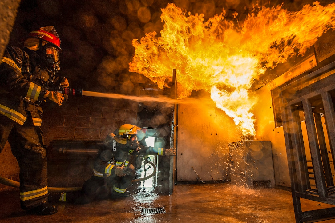 An airman sprays flames with a hose inside a room, as another firefighter observes.