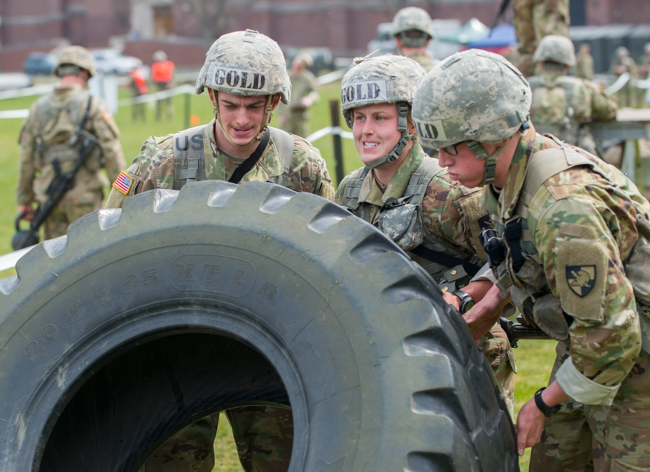 West Point cadets roll a tractor tire during training.