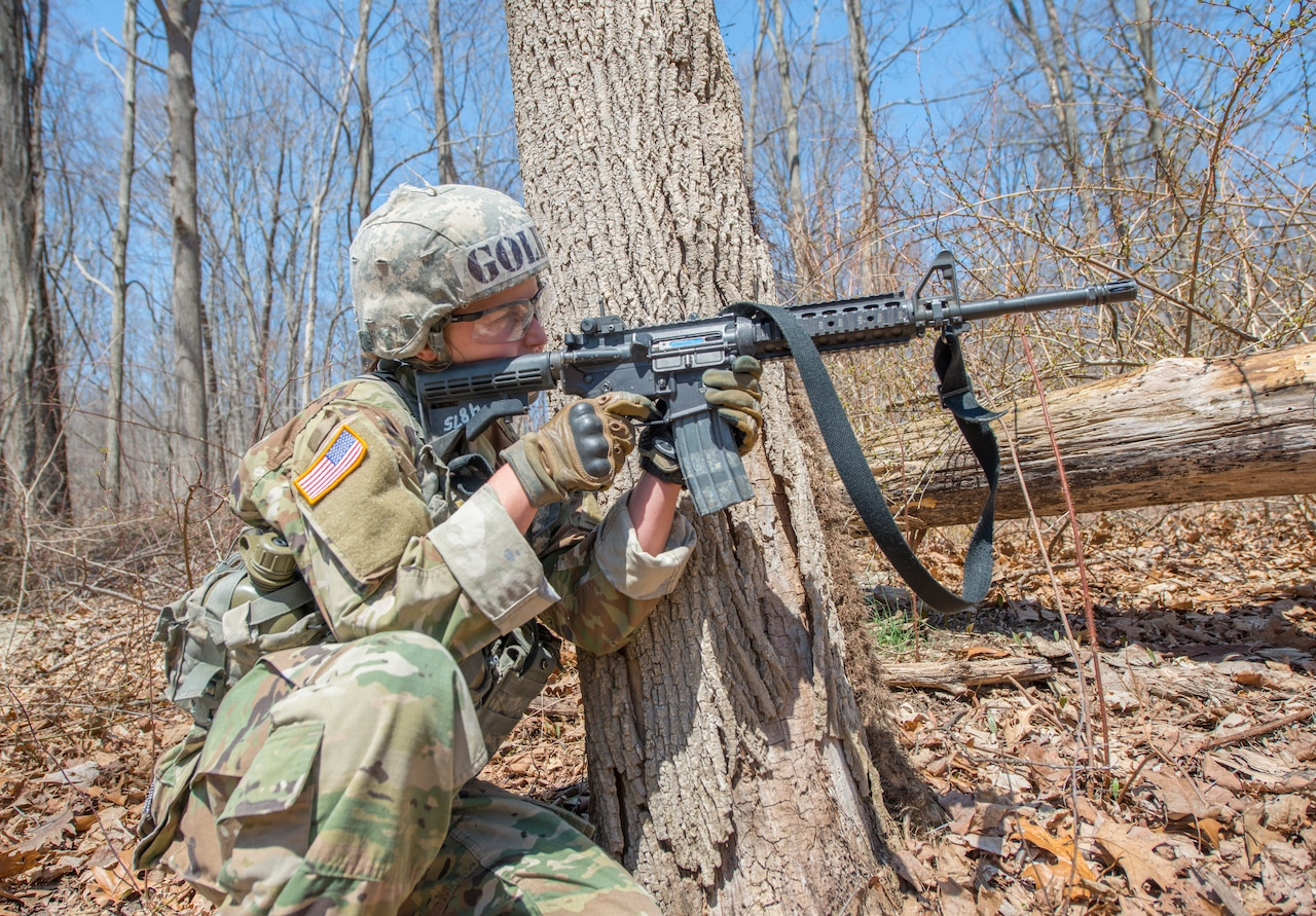 A West Point cadet fires a rifle.