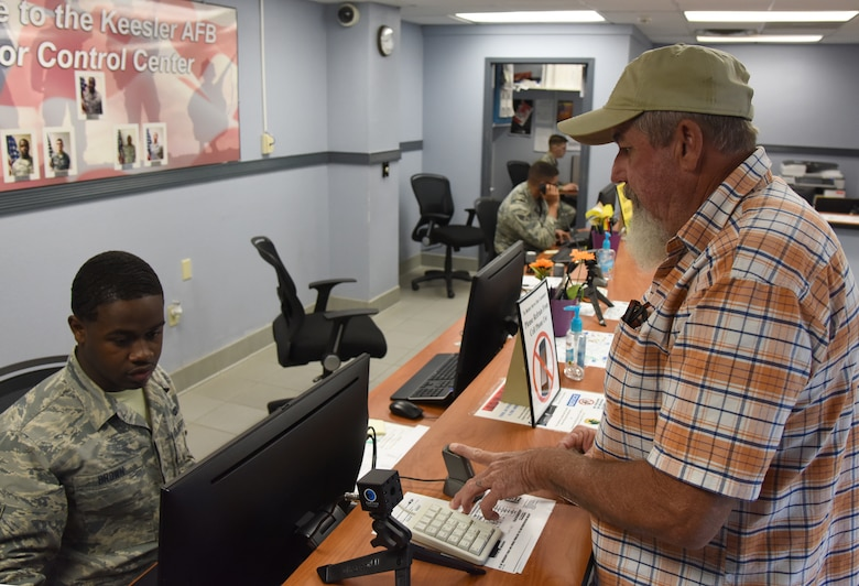 Airman 1st Class Leonard Brown, 81st Security Forces visitors center clerk, provides a Gold Star Family Member ID card to Joey Roberts, Gold Star Family Member at the visitor center at Keesler Air Force Base, Mississippi, April 24, 2018. As a surviving parent of a killed in action service member, Roberts is allowed to obtain an ID card for recognition and installation access so he can attend events and access Airmen and Family Readiness Center referral services. (U.S. Air Force photo by Kemberly Groue)