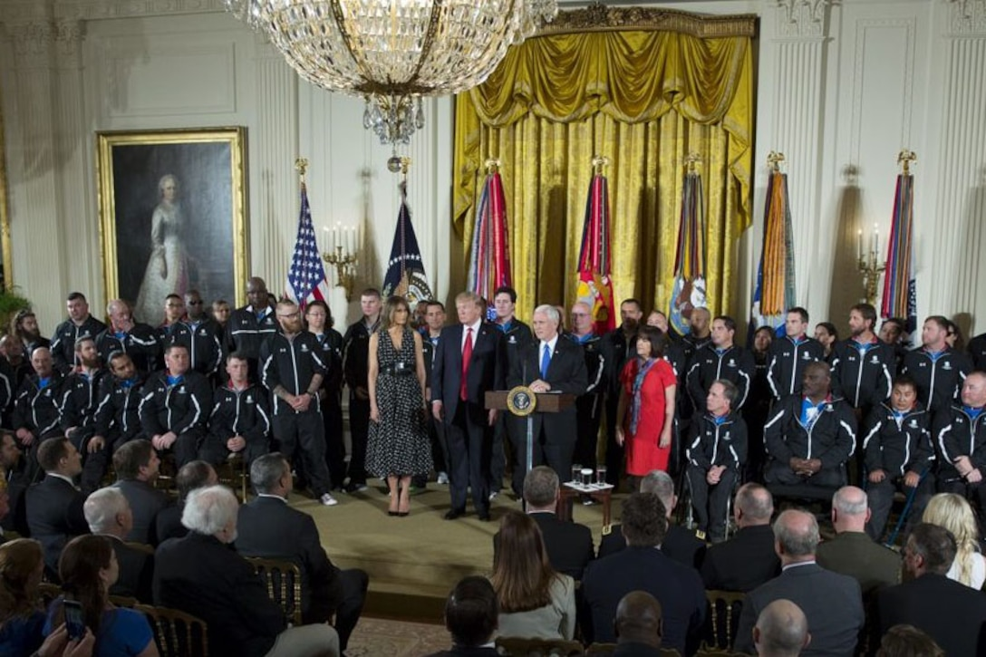 The president and vice president stand on stage with wounded warriors.