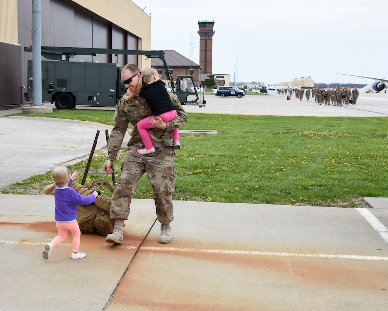 An Airman picks up his two daughters while a line of returning Airmen approach behind him.