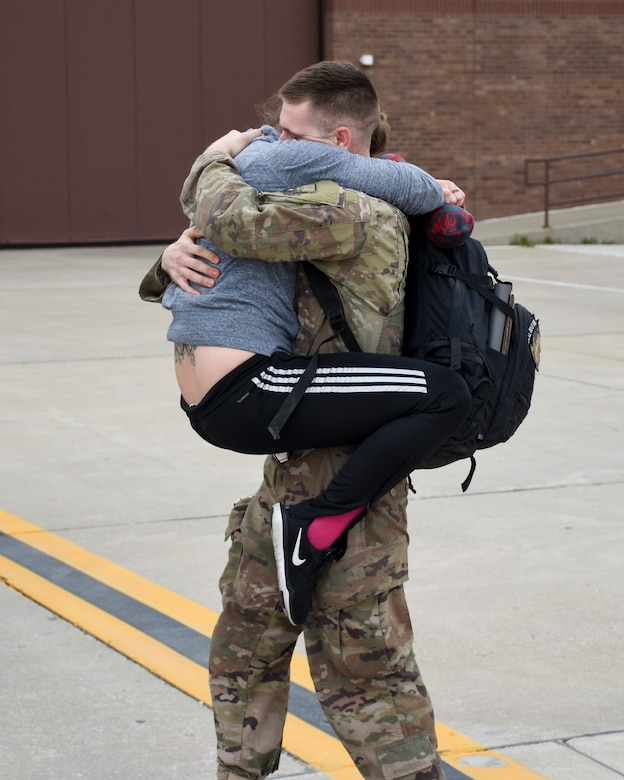 A woman leaps into the arms of her returning Airman as he approaches the waiting families outside the 5-bay.