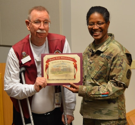 Army Col. Traci Crawford, Brooke Army Medical Center deputy commanding officer, poses for a photo with Patrick Spencer, BAMC Retiree Activities Group Volunteer of the Year, during the BAMC Volunteer Recognition Ceremony April 16.