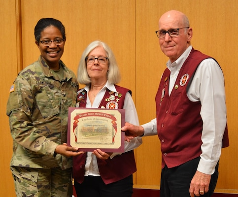 Army Col. Traci Crawford, Brooke Army Medical Center deputy commanding officer, poses for a photo with Barbara and Ed Bowles, BAMC Family of the Year, during the BAMC Volunteer Recognition Ceremony April 16.